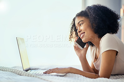 Buy stock photo Shot of a young woman relaxing in bed and using a mobile phone and laptop