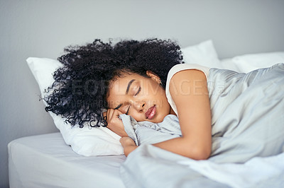 Buy stock photo Shot of a young woman sleeping peacefully in her bed