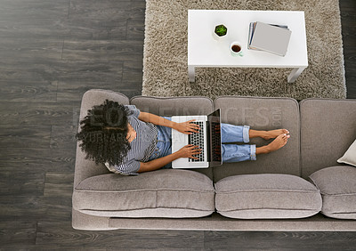 Buy stock photo High angle shot of a young woman using a laptop on the sofa at home