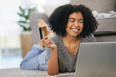 Buy stock photo Shot of an attractive young woman using a laptop and credit card at home