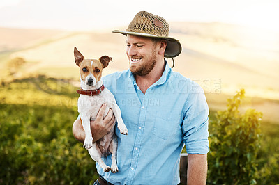 Buy stock photo Shot of a farmer holding his dog in a vineyard