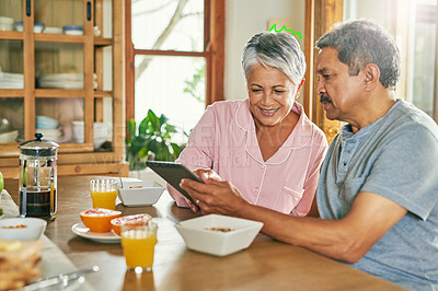 Buy stock photo Shot of a cheerful elderly couple browsing on a digital tablet together while having breakfast around a table at home