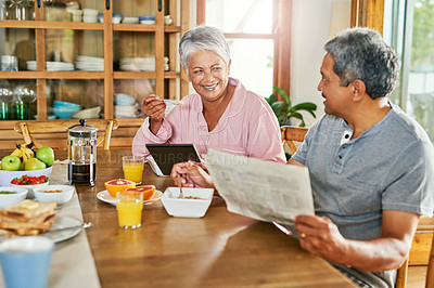 Buy stock photo Shot of a carefree elderly couple having breakfast together while reading the paper and browsing on a digital tablet at home