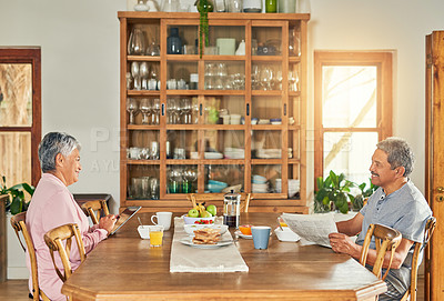 Buy stock photo Shot of a cheerful elderly couple having breakfast together around a table at home during the day