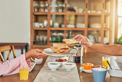 Buy stock photo Shot of an unrecognizable woman handing over a plate of toast to a man during breakfast at home