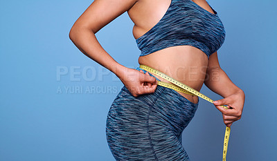 Buy stock photo Cropped shot of an unrecognizable woman measuring her waist