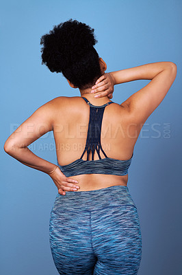 Buy stock photo Studio shot of a young woman suffering from back pain