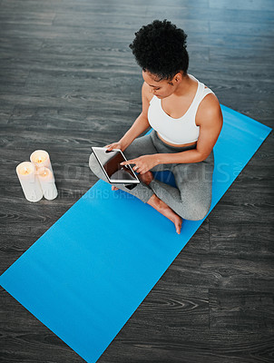 Buy stock photo Shot of a young woman following yoga instructions on her digital tablet