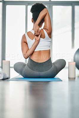 Buy stock photo Rearview shot of a young woman practising a yoga position