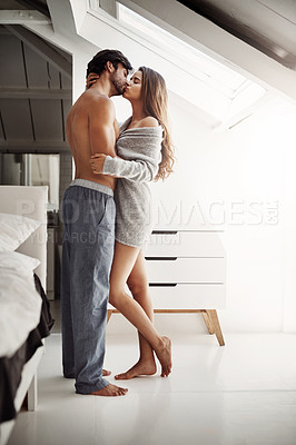 Buy stock photo Shot of an affectionate young couple in their bedroom at home