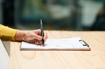 Buy stock photo Closeup shot of an unrecognizable woman filling in paperwork on a clipboard at a table