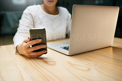 Buy stock photo Closeup shot of an unrecognizable woman using a cellphone and laptop