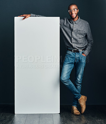 Buy stock photo Shot of a handsome young man standing next to a blank placard