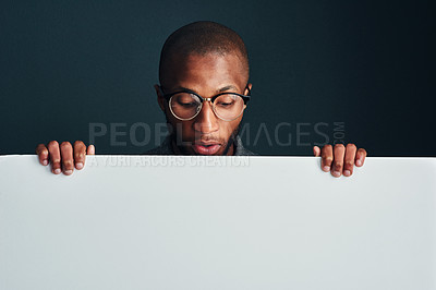 Buy stock photo Cropped shot of a man standing behind a blank placard