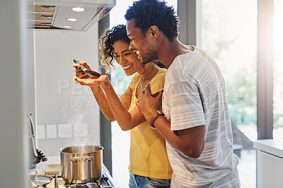 Buy stock photo Cropped shot of a young married couple tasting the food they are making in the kitchen at home