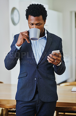 Buy stock photo Cropped shot of a handsome young man drinking coffee and using a cellphone at home
