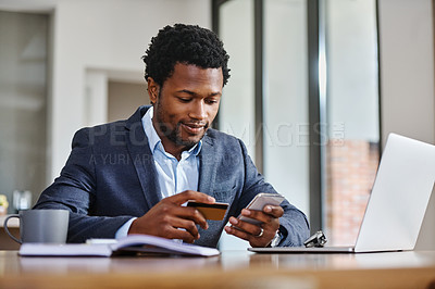 Buy stock photo Cropped shot of handsome young man using a credit card and cellphone while working from home