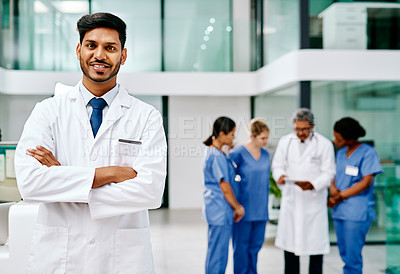 Buy stock photo Portrait of a doctor standing in a hospital with his colleagues in the background