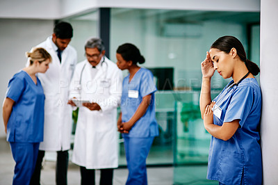 Buy stock photo Shot of a a nurse looking stressed out while standing in a hospital with her colleagues in the background