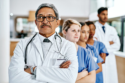 Buy stock photo Shot of a group of medical practitioners standing in a row in a hospital