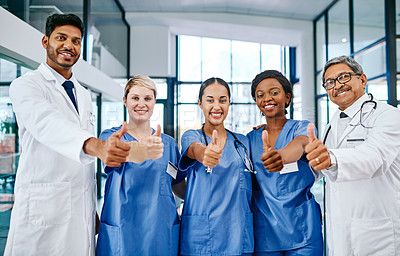 Buy stock photo Portrait of a group of medical practitioners showing thumbs up while standing in a hospital