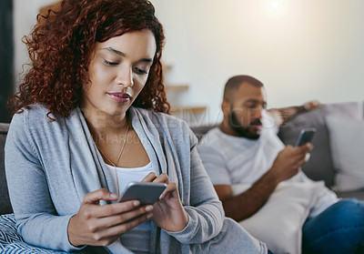 Buy stock photo Cropped shot of a young woman looking upset while sending a text after having an argument with her boyfriend