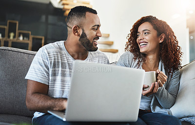 Buy stock photo Cropped shot of an affectionate young couple using their laptop while relaxing on the sofa at home