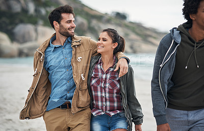 Buy stock photo Shot of a young couple walking with friends along the beach