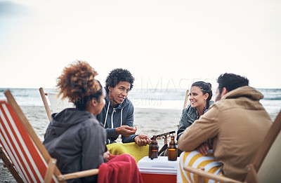 Buy stock photo Shot of a group of young friends hanging out and having drinks at the beach