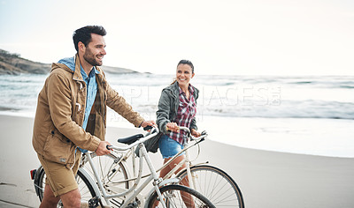 Buy stock photo Shot of a couple walking on the beach with their bicycles