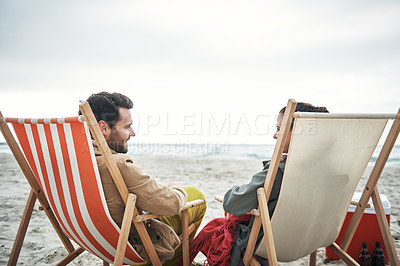 Buy stock photo Shot of a young couple relaxing on the beach