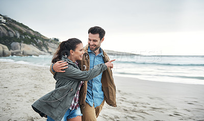 Buy stock photo Shot of a young couple enjoying a stroll on the beach