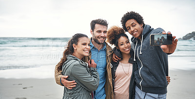 Buy stock photo Shot of a group of young friends taking a selfie together at the beach