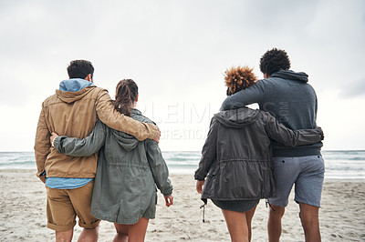 Buy stock photo Rearview shot of a group of young friends walking together along the beach