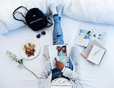 Buy stock photo High angle shot of an unrecognizable woman reading a magazine and having breakfast on her bed in her bedroom at home