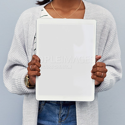 Buy stock photo Studio shot of an unrecognizable young woman holding a blank tablet against a grey background