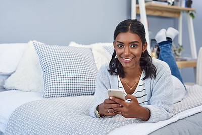 Buy stock photo Shot of an attractive young woman using a cellphone and chilling on her bed in her bedroom at home