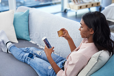 Buy stock photo Cropped shot of an attractive young woman using a cellphone and credit card while chilling on the sofa at home