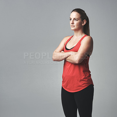 Buy stock photo Studio shot of an athletic young woman standing with her arms crossed against a grey background