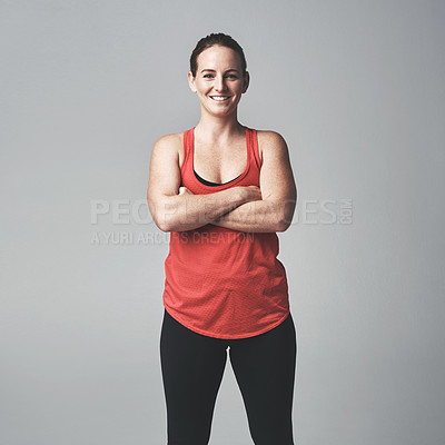 Buy stock photo Studio portrait of an athletic young woman standing with her arms crossed against a grey background