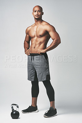 Buy stock photo Studio portrait of a shirtless young man standing with his hands on his hips against a grey background