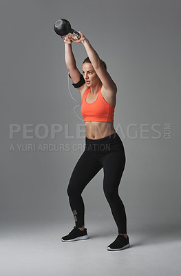 Buy stock photo Studio shot of an athletic young woman working out with a kettle bell against a grey background