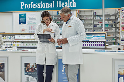 Buy stock photo Shot of two pharmacists having a discussion in a chemist