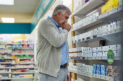 Buy stock photo Shot of a mature man browsing the shelves of a pharmacy and coughing