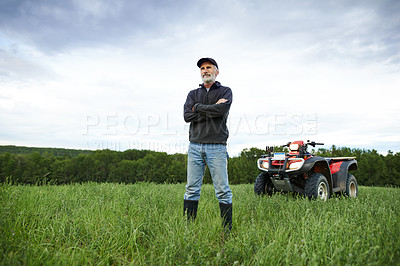 Buy stock photo Shot of a mature farmer standing on a field with a quad bike in the background