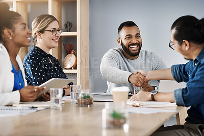 Buy stock photo Shot of two young businessmen shaking hands during a meeting with colleagues in a modern office