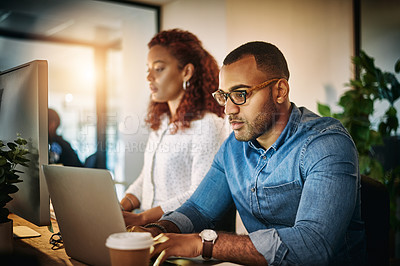 Buy stock photo Shot of a young businessman using a laptop with his colleague next to him during a late night at work