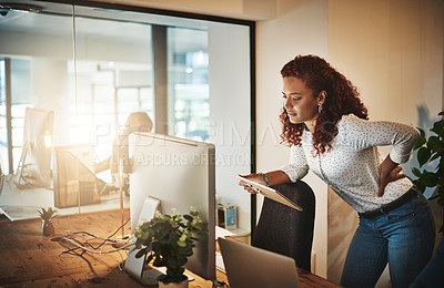 Buy stock photo Shot of a young businesswoman suffering from backache while working at her desk during a late night at work
