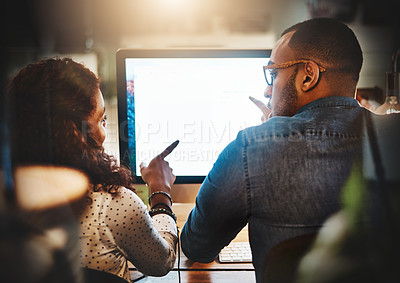 Buy stock photo Rearview shot of a young businessman and businesswoman using a computer together during a late night at work