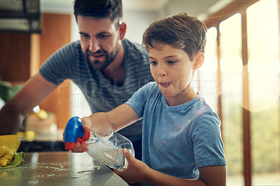 Buy stock photo Shot of a father and son cleaning the kitchen counter together at home